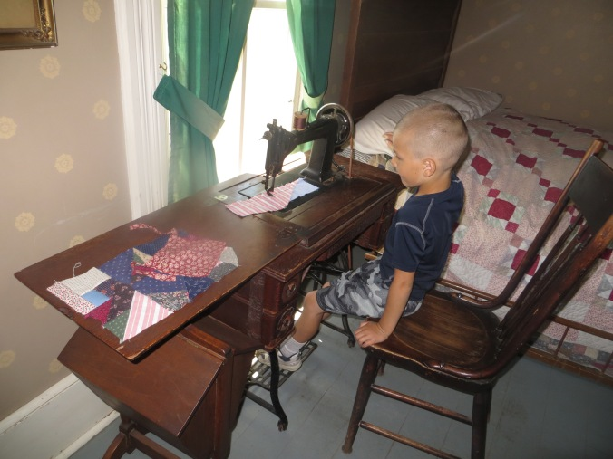 Lewis attempting to sew at Living History Farms.