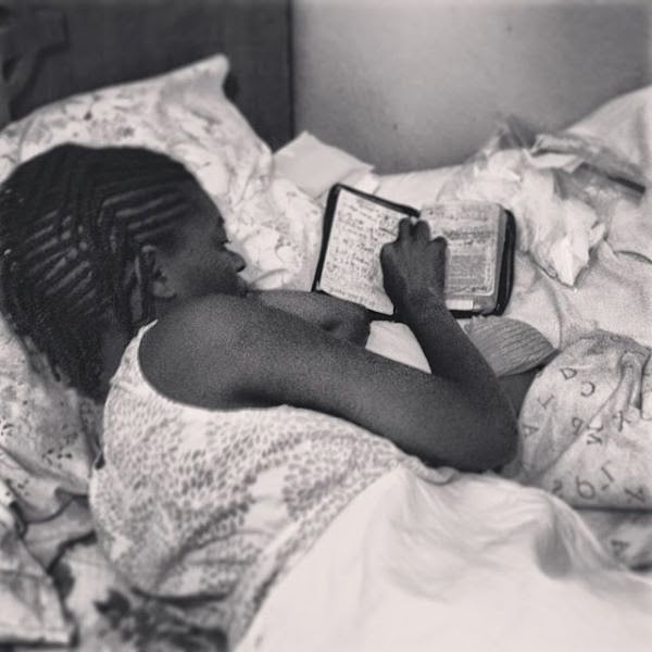 New mom reading her Bible with baby by her side. (photo taken from livesay haiti weblog.)